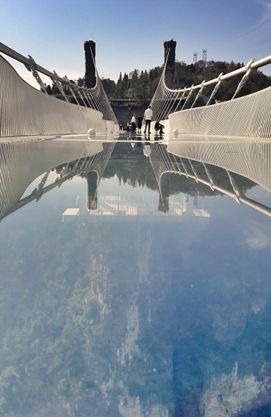 The glass bridge connects two mountains. It has a length of 1,411 ft,, 20 feet wide and a height of 984 feet.